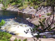 Folket spelar och simmar på den naturliga vattenglidbanan som lokaliseras på Barron River arkivbilder