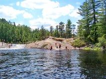 Folket spelar och simmar på den naturliga vattenglidbanan som lokaliseras på Barron River royaltyfri foto