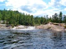 Folket spelar och simmar på den naturliga vattenglidbanan som lokaliseras på Barron River royaltyfri fotografi
