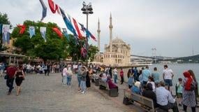 Folket spenderar tid och tycker om sikten i Ortakoy med moskén och bosphorusen, Istanbul, Turkiet royaltyfria bilder