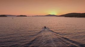 Folket svävar på ett fartyg på havet i aftonen lager videofilmer