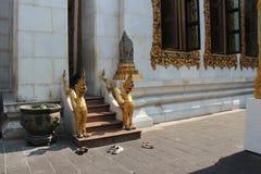 Folket tog bort deras skor, innan de gick in i den huvudsakliga korridoren av en buddistisk tempel (Thailand) Arkivbild