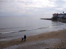 Folket tycker om att gå till och med den Antalya sidan på stranden i en solig dag arkivfoto