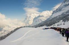 Folket tycker om bergsikten som väntar i linje för att ta delen i det årliga Horn-pulkan loppet från Alpiglen till Grund i Grinde Arkivfoto