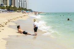 Folket tycker om för att koppla av nära pir i Sunny Isles Beach Royaltyfri Bild
