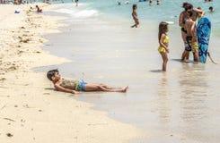 Folket tycker om för att koppla av nära pir i Sunny Isles Beach Arkivbild
