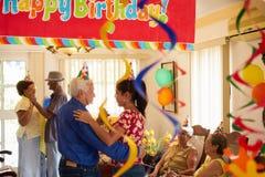 Folket tycker om födelsedagpartiet med vänner i geriatriskt sjukhus Arkivfoto