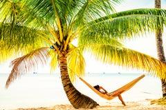 Folket tycker om semester på den tropiska sandiga stranden på bakgrundshavsvatten och blå himmel Royaltyfri Bild
