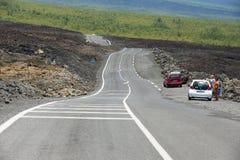 Folket tycker om sikten till asfaltvägen över vulkanisk lava i Sainte-Ros De La Möte, Frankrike Royaltyfria Bilder