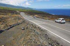 Folket tycker om sikten till asfaltvägen över vulkanisk lava i Sainte-Ros De La Möte, Frankrike Royaltyfri Foto