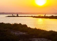 Folket tycker om sjösidafiske och tabilder på solnedgången Arkivbild