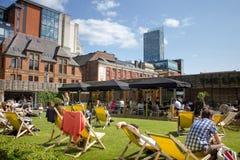 Folket tycker om solsken i centrum Spinningfields Manchester UK arkivfoton