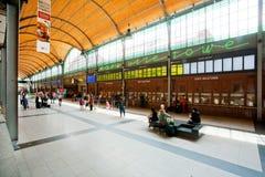 Folket väntar på drev i den enorma ljusa korridoren av järnvägsstationen Royaltyfria Foton