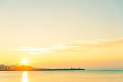 Folket vaggar på pir med det lugna havet på solnedgången i italiensk stad av trieste Arkivfoton