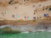 Folket vilar på den lösa stranden med deras familjer arkivfoton