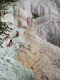 Folket vilar p? det termiskt saltar vattenfall av de mineraliska v?rarna av Bagni San Filippo p? en solig dag arkivfoton