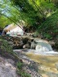 Folket vilar p? det termiskt saltar vattenfall av de mineraliska v?rarna av Bagni San Filippo p? en solig dag royaltyfri foto