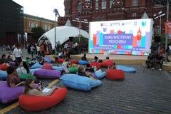 Folket vilar sammanträde på de färgrika mjuka stolarna Arkivfoto