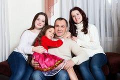 Folkfamilj, jul och adoptionbegrepp - lycklig moder, fader och barn som hemma kramar nära en julgran arkivbilder