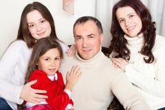 Folkfamilj, jul och adoptionbegrepp - lycklig moder, fader och barn som hemma kramar nära en julgran arkivfoton