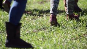 Folkfot som går på ett grönt gräs lager videofilmer