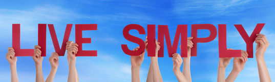Folkhänder som rymmer det röda raka ordet Live Simply Blue Sky Arkivbild