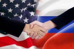 Folkhandskakning med ryssen och amerikanska flaggorna royaltyfri bild