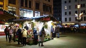 Folkköpandeblommor på den huvudsakliga julmarknaden på Vorosmarty fyrkantVörösmarty tér stock video