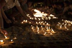 Folkljusstearinljus som betalar respekt till den buddha reliken Arkivfoton