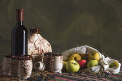 Folklore table with ethnic carpet, sweet wine, jug, glasses, apples Stock Images