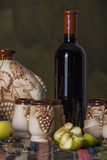 Folklore table with ethnic carpet, sweet wine, jug, glasses, apples Stock Image