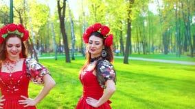 Folkloredans door Oekraïense vrouwen in heldere kostuums en bloemcirclets stock footage
