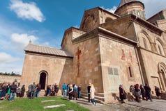 Folkmassa av be män och kvinnor runt om väggarna av den Svetitskhoveli domkyrkan Lokal för Unesco-världsarv Royaltyfri Fotografi