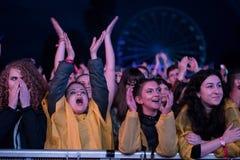 Folkmassa av bifallfolk som tycker om en levande konsert Royaltyfria Bilder