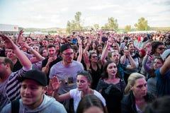 Folkmassa av bifallfolk som tycker om en levande konsert Arkivfoton