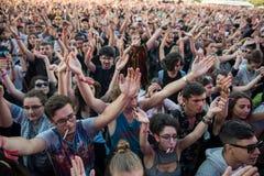 Folkmassa av bifallfolk som tycker om en levande konsert Royaltyfria Foton