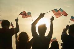 Folkmassa av den hållande amerikanska flaggan för folk, baksidasikt royaltyfria foton
