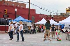 Folkmassa av folk inklusive pojke på skateboarden och barn med bubblor som är främsta av tält på den blåa kupolgatamässan i Tulsa Royaltyfria Bilder