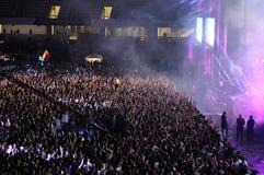 Folkmassa av folk med lyftta händer på en konsert Royaltyfria Bilder