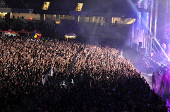 Folkmassa av folk med lyftta händer på en konsert Arkivfoto