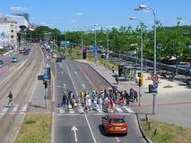 Folkmassa av folk på övergångsställe, bilar, rött rött ljus, vägmärken Royaltyfri Foto