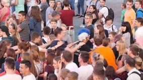 Folkmassa av folk som dansar på en fyrkant under TV-sändning av fotbollsmatchen Materiellängd i fot räknat Fotbollsfan arkivfilmer