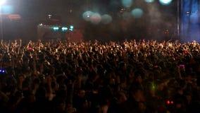 Folkmassa av folk som dansar på konserten lager videofilmer