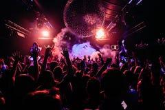 Folkmassa av folk som dansar på nattklubben arkivfoton