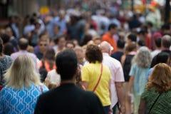 Folkmassa av folk som går på gatatrottoaren Arkivfoto