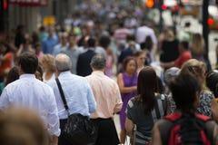 Folkmassa av folk som går på gatatrottoaren Arkivfoton