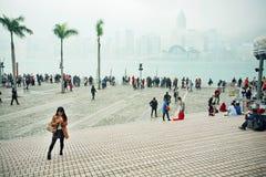 Folkmassa av folk som går på pir av Victoria Harbor med cityscape i dimma royaltyfri bild
