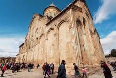 Folkmassa av folk som går runt om den berömda ortodoxa Svetitskhoveli domkyrkan som byggs i det 4th århundradet i Georgia Royaltyfri Bild