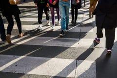 Folkmassa av folk som korsar en gata Arkivfoto