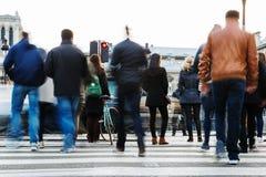 Folkmassa av folk som korsar en stadsgata Royaltyfri Foto